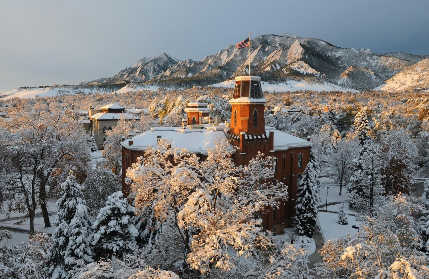 The majestic, snow-covered Flatirons is a breathtaking backdrop with Old Main at the University of Colorado Boulder in the foreground. (Photo by Casey A. Cass/University of Colorado)